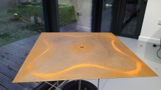 a square sheet of steel with a delicate pattern made of an orange sand line in the shape of simple butterfly wings.