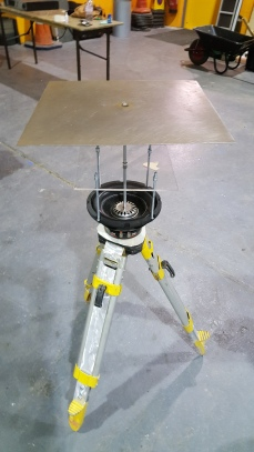 point of view from above looking down on a metal plate attached by a central rod to a speaker standing on rugged yellow black and silver tripod legs